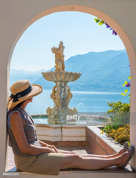 Woman relaxes besides fountain overlooking lake