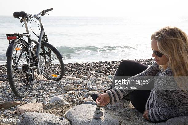 Woman relaxes by bike on beach, zen rock pile