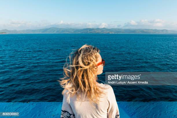 woman relaxes during ferry crossing, sunrise - leanincollection stock pictures, royalty-free photos & images