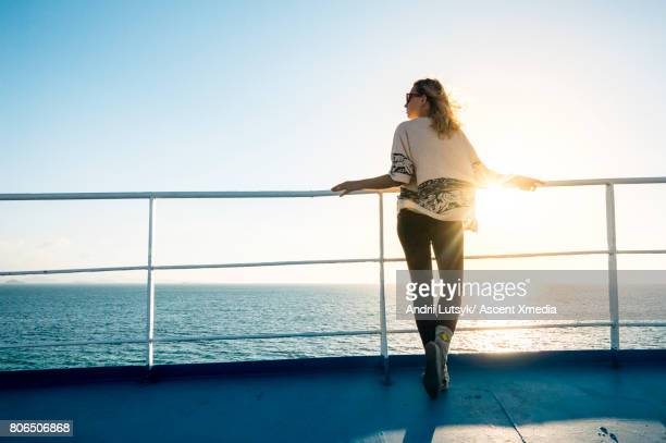 woman relaxes during ferry crossing, sunrise - fähre stock-fotos und bilder