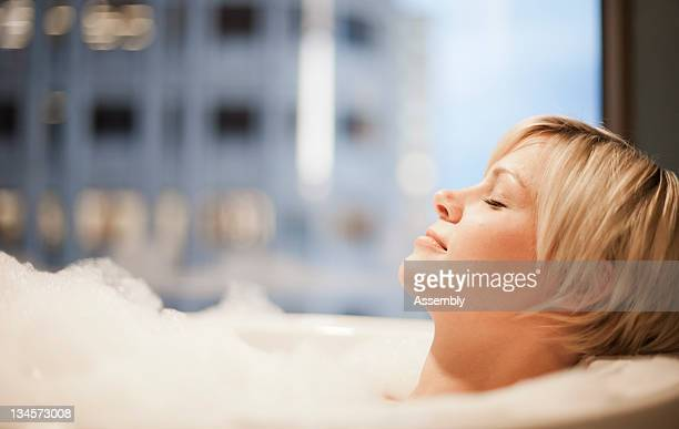Woman relaxes in a bubble bath.