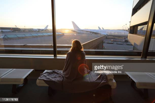 woman relaxes in airport lobby, planes in distance - narita stock pictures, royalty-free photos & images
