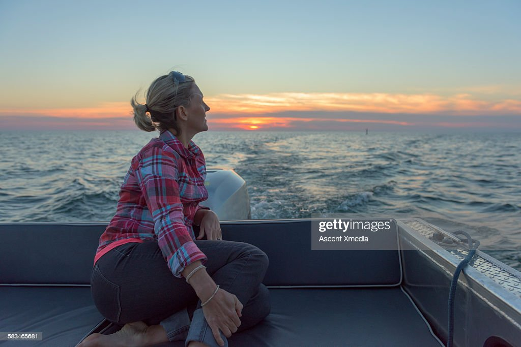 Woman relaxes in boat stern, looks off across lake : Stock Photo