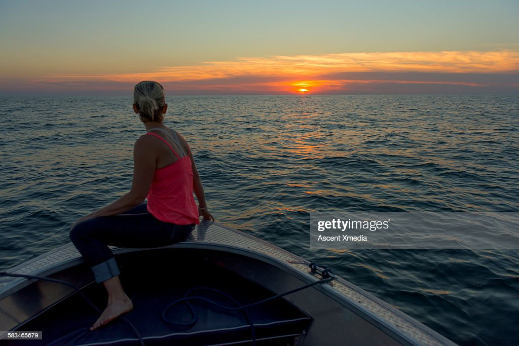 Woman relaxes in bow of boat,looks towards sunrise : Stock Photo