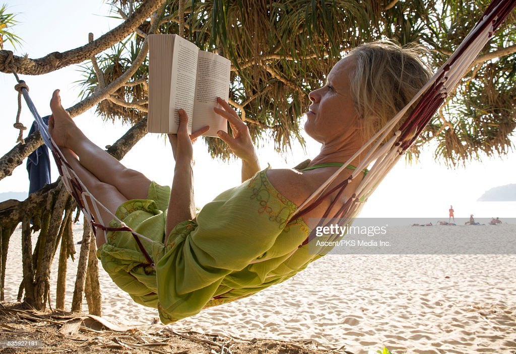 Woman relaxes in hammock, reading book : Stock Photo