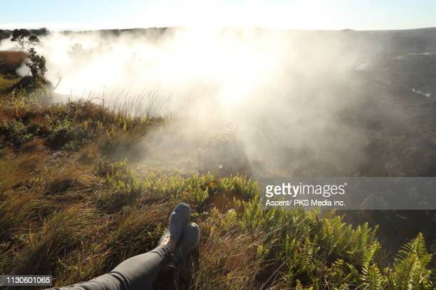 woman relaxes in meadow and watches sunrise over mist - partie inférieure photos et images de collection
