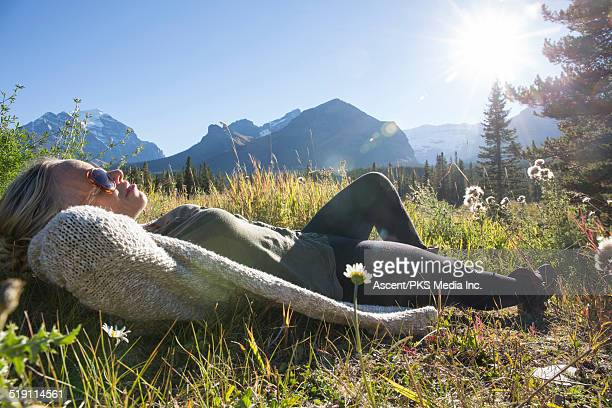 woman relaxes in mountain meadow, wildflowers - シュラッグ ストックフォトと画像