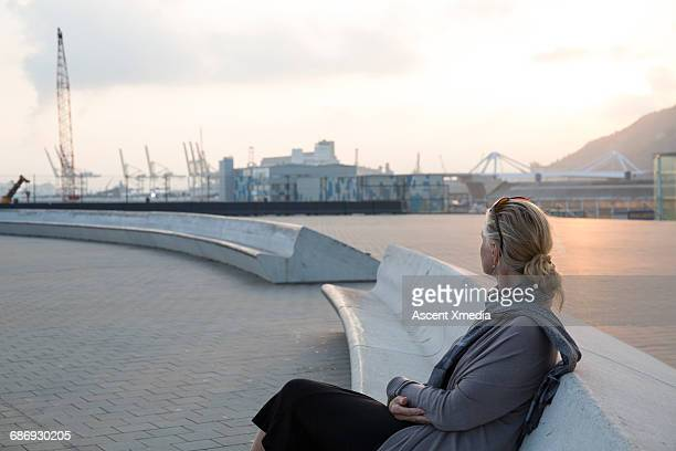 Woman relaxes in port area, watching sunrise