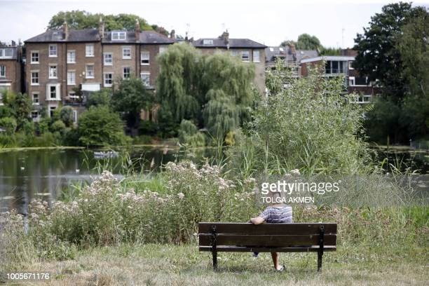 A woman relaxes on a bench on Hampstead Heath in London on July 26 2018 Britain has been in the grip of its longest heatwave in decades sparking...