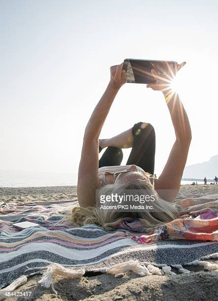 Woman relaxes on beach, uses digital tablet