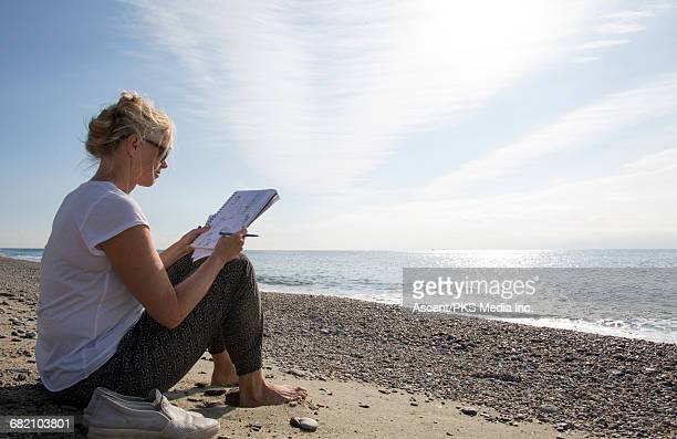 Woman relaxes on beach, with sketch pad