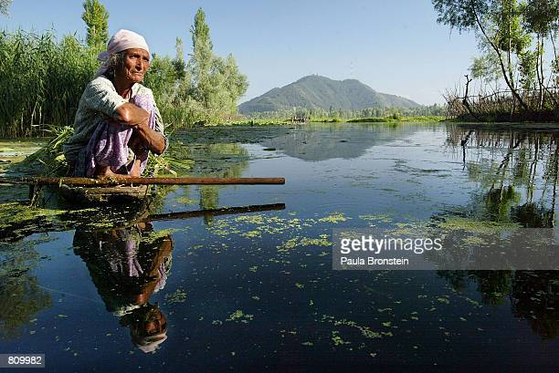 Woman relaxes on Lake Dal after collecting seaweed to be used as fertilizer for her garden June 22, 2002 in Srinagar, the summer capital of the...