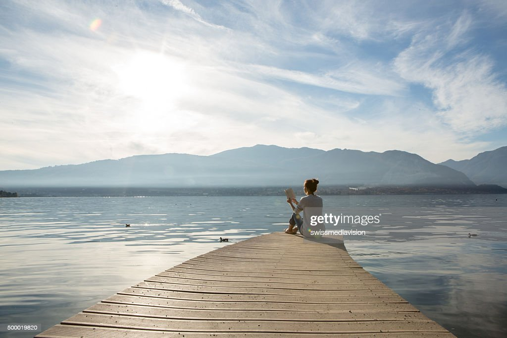 Woman relaxes on lake pier, reads a book : Stock Photo