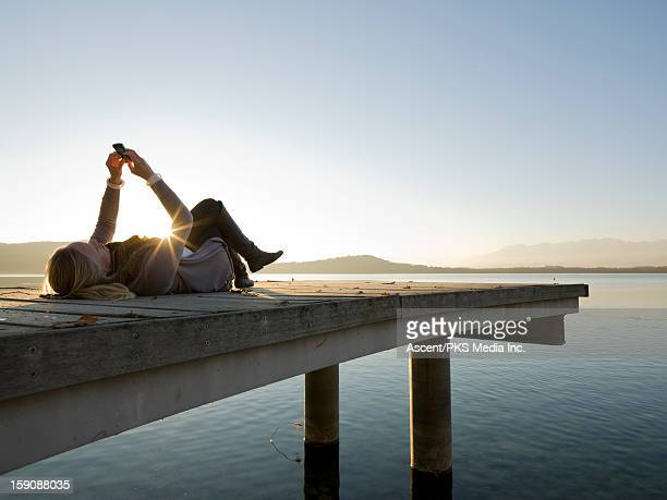 Woman relaxes on lake pier, sending text