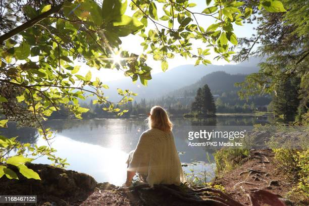 woman relaxes on mountain lakeshore at sunrise - ambientazione tranquilla foto e immagini stock