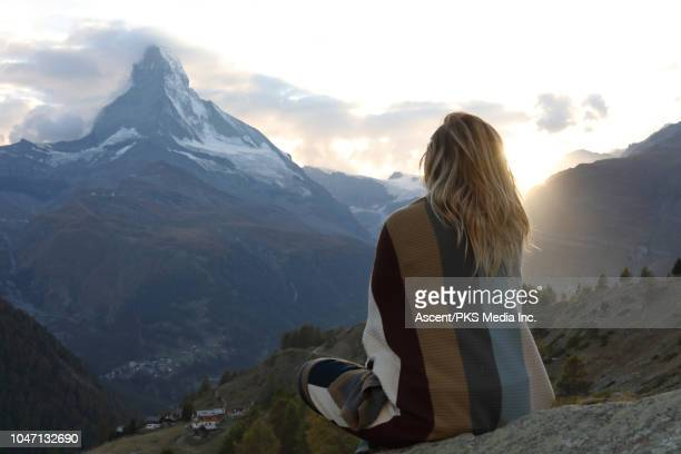 woman relaxes on rock ledge, nestles into blanket - schöne natur stock-fotos und bilder