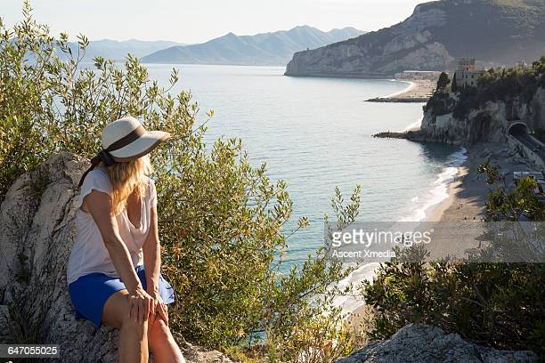 Woman relaxes on rocks above beach, coastline