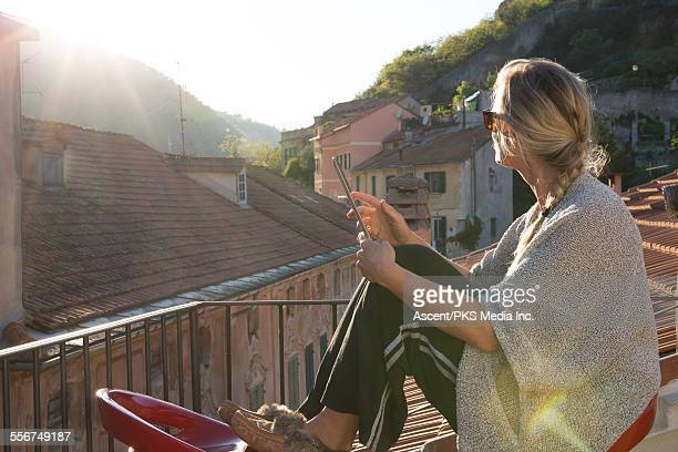 Woman relaxes on rooftop terrace, digital tablet
