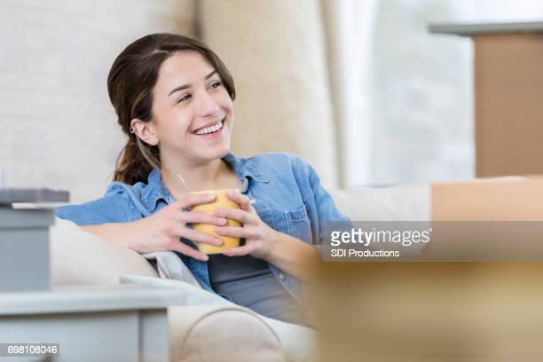 Woman relaxes on the couch of her new home