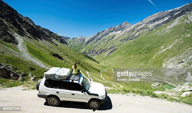 Woman relaxes on top of 4x4, looks down road climb