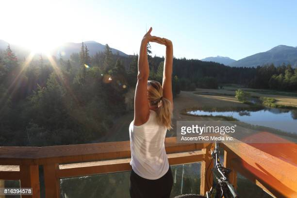 woman relaxes on veranda, looks out to mountains - sleeveless top stock pictures, royalty-free photos & images