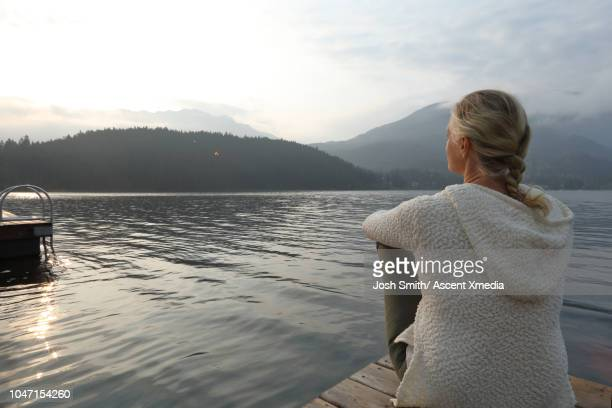 woman relaxes on wooden lake pier, at sunrise - three quarter length stock pictures, royalty-free photos & images