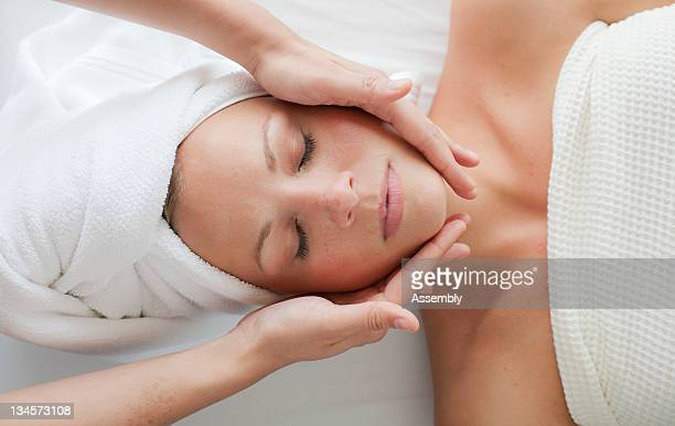 A woman relaxes while getting a facial.