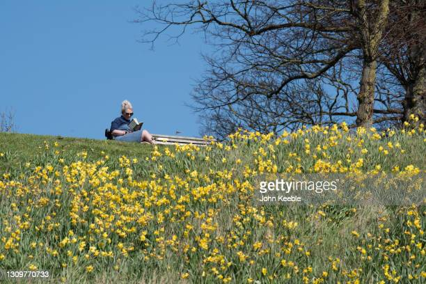 Woman relaxes while reading a book in the sun during the warm weather on March 29, 2021 in Southend, England. Today the government eased its rules...