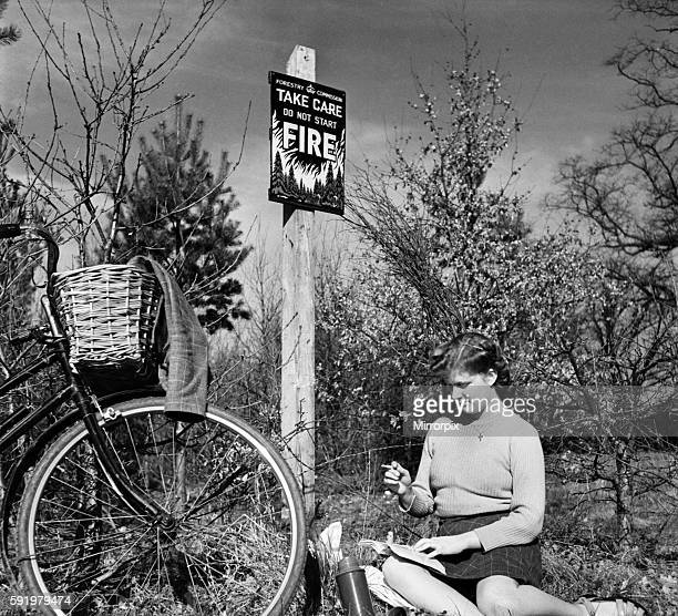Woman relaxes with a book next to her bicycle next to a Risk of Fire sign in Thetford Forest whilst smoking a cigarette O7522001