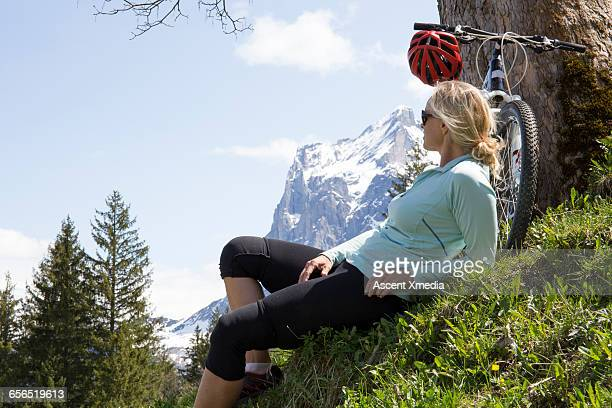 Woman relaxes with bike below tree, snowy mtns