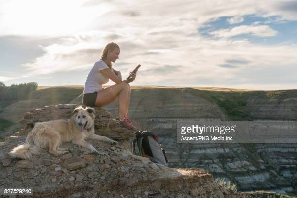 Woman relaxes with dog on hillside above badlands