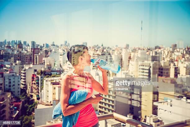 Frau entspannend nach Übungen in einem Fitnessstudio auf dem Dach