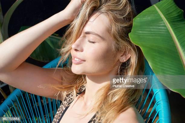 Woman relaxing amongst tropical plants