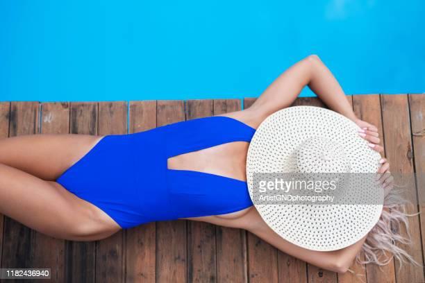 woman relaxing around poolside. - swimwear stock pictures, royalty-free photos & images