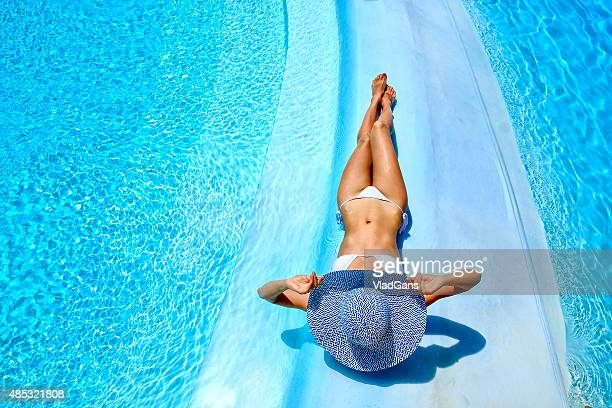 woman relaxing at a resort swimming pool - blue hat stock pictures, royalty-free photos & images