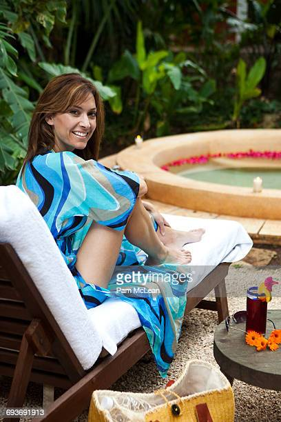 Woman relaxing at an outdoor tropical spa pool