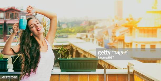 woman relaxing at balcony with morning coffee - penthouse girl stock photos and pictures