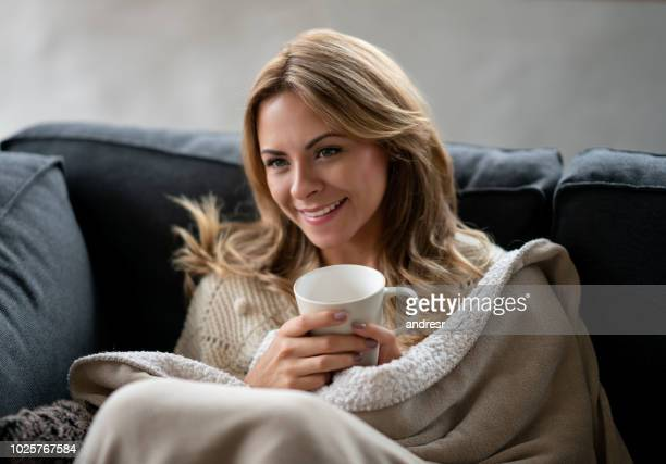 woman relaxing at home drinking a cup of coffee - blanket stock pictures, royalty-free photos & images