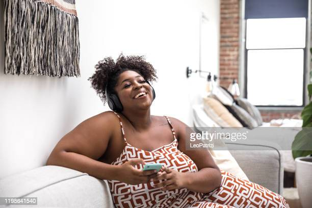 woman relaxing at home listening to music - podcasting stock pictures, royalty-free photos & images