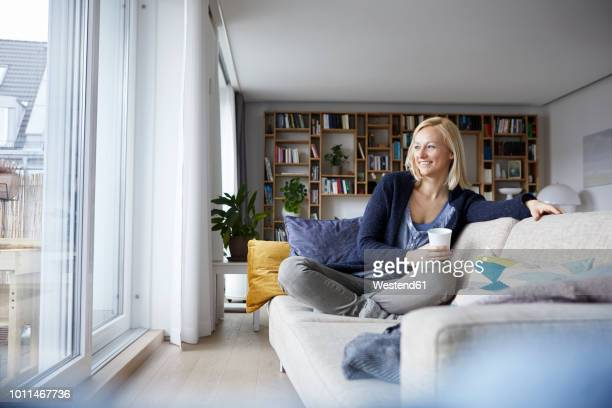 woman relaxing at home, sitting on couch - hygge stock pictures, royalty-free photos & images