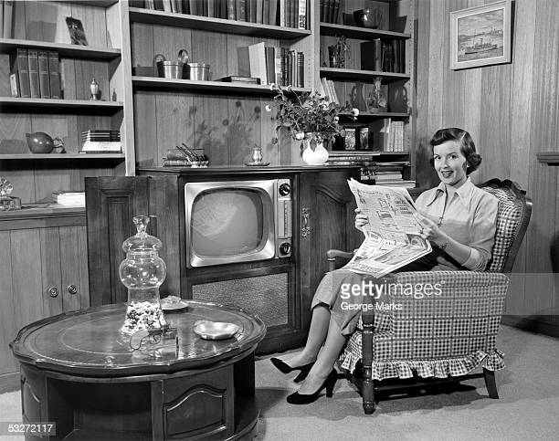 woman relaxing at home with newspaper - tv housewife stock photos and pictures