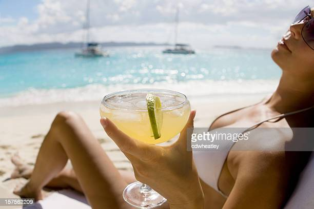 woman relaxing at the beach drinking margarita cocktail