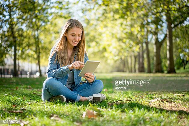 Woman relaxing at the park using a tablet computer