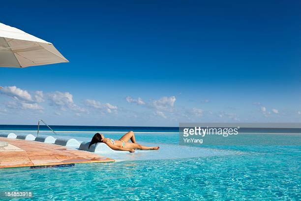 woman relaxing at tourist resort hotel infinity swimming pool, mexico - serene people stock pictures, royalty-free photos & images