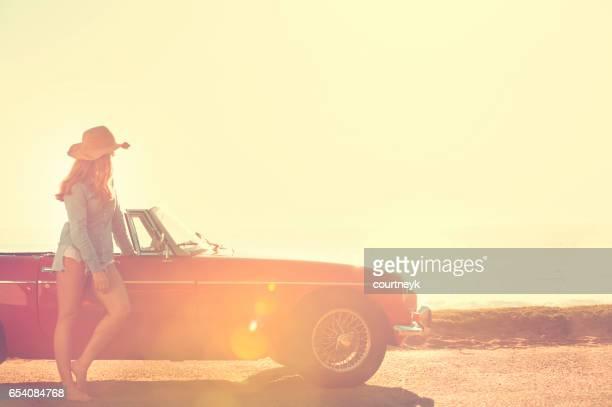 Woman relaxing beside a car.