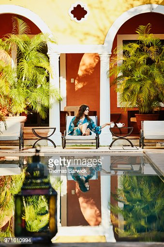 Woman relaxing by hotel pool drinking tea