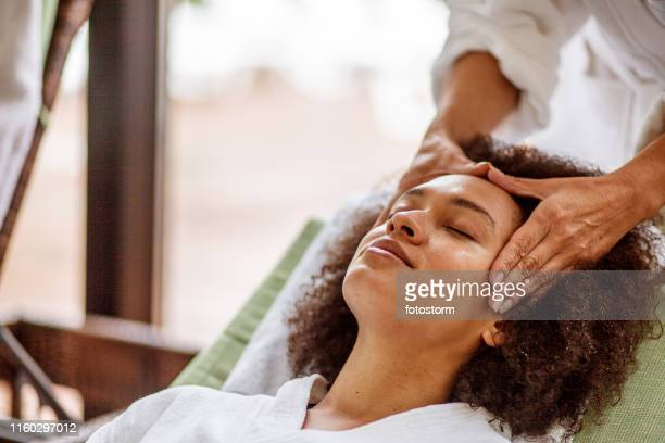 woman relaxing during head massage - massage stock pictures, royalty-free photos & images
