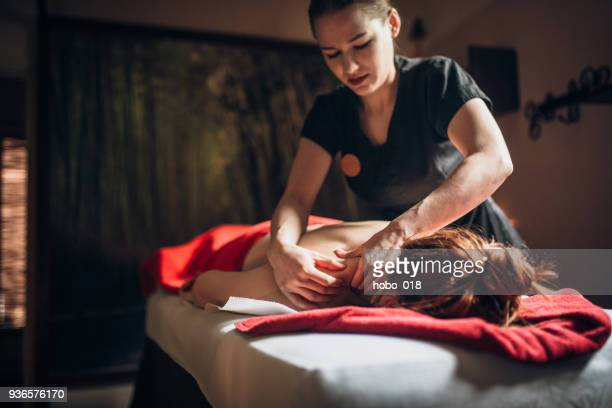 woman relaxing during massage at the spa - massage oil stock pictures, royalty-free photos & images