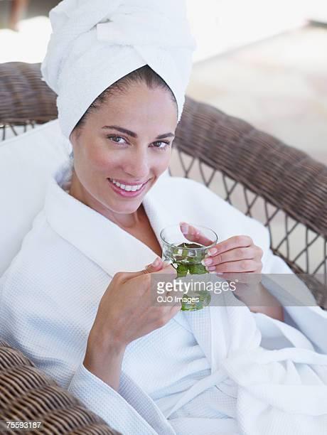 Femme se détendre dans un peignoir en tenant une boisson de remise en forme