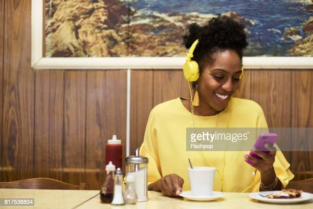 Woman relaxing in a cafe using phone and listening to music